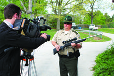 """<div class=""""source"""">Kentucky Department of Agriculture</div><div class=""""image-desc"""">Capt. Todd Rogers, a conservation officer with the Kentucky Department of Fish and Wildlife Resources, displays one of the rifles that were put up for auction for a TV crew today in Frankfort. </div><div class=""""buy-pic""""></div>"""