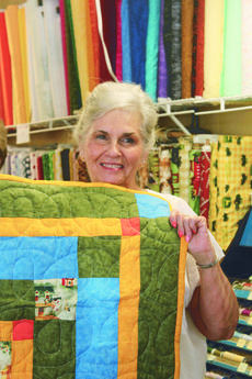"<div class=""source"">Bobbie Lanham</div><div class=""image-desc"">Shirley Jones of Shirley's Fabrics holds a quilt she made. The shop on Lincoln Boulevard has fabrics and notions.</div><div class=""buy-pic""><a href=""/photo_select/42641"">Buy this photo</a></div>"