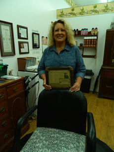 """<div class=""""source"""">Vanessa Hurst</div><div class=""""image-desc"""">Kathy Stillwell holds the article that originally appeared in the LaRue County Herald News on November 7, 2001. The article states """"… 'lower yur ears and tan yur hide' …along with 'ear lowerin' she offers 'warsh and curl' 'permatizin' 'streakin' 'colorin' and 'pluckin.'"""" </div><div class=""""buy-pic""""><a href=""""/photo_select/44840"""">Buy this photo</a></div>"""