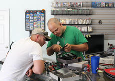 "<div class=""source"">Doug Ponder</div><div class=""image-desc"">Games R US owner Joey Halprin (right) fixes a NES gaming system for Michael Garrett of Campbellsville (left). </div><div class=""buy-pic""><a href=""/photo_select/42259"">Buy this photo</a></div>"