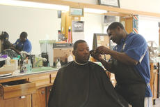 """<div class=""""source"""">Photo by Doug Ponder</div><div class=""""image-desc"""">Tino's Barber Shop owner Tino Cobb gives Chris Williams of Elizabethtown a haircut. Cobb is an assistant coach of the LaRue County High School football team and Williams is an assistant coach of the Elizabethtown High School football team.  </div><div class=""""buy-pic""""><a href=""""/photo_select/43213"""">Buy this photo</a></div>"""