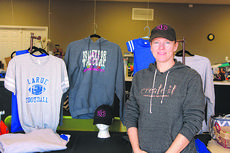 """<div class=""""source"""">Doug Ponder</div><div class=""""image-desc"""">Create It specializes in custom vinyl graphics printing for window decals, banners, signs, clothing, license plates, blankets, backpacks and much more. The business also works with school groups to help in their fundraising efforts. Owner Melissa Longhofer is shown standing with  clothing that was designed for LaRue County sports program fundraisers and Volleyball for the Cure. </div><div class=""""buy-pic""""><a href=""""/photo_select/44892"""">Buy this photo</a></div>"""