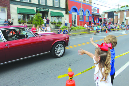 Children wave at a classic car for candy on Saturday during the 2017 Rolling Fork Iron Horse Festival in New Haven.