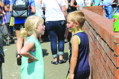 Travis Riley, 6, and Bella Dearinger, 5, blow gum bubbles at each other after the parade.
