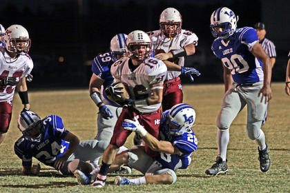 Cody Thompson and Matthew Hornback bring down the Henry County quarterback. Blake Heibert is at right.
