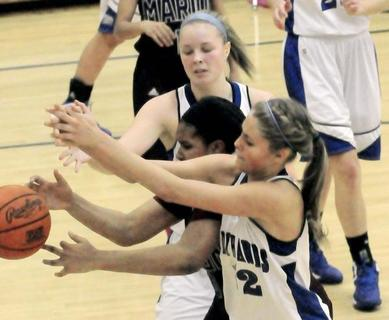 LaRue County's Ivy Brown, back, and Alisha Durbin double team Marion County's Logan Powell to knock the ball away Tuesday night.