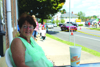 Catherine Jackson, 63, sits along the parade route on Main Street in New Haven.
