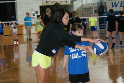 Lady Hawk senior Sadie Peters demonstrated serving to Layla Ward at Wednesday's  volleyball clinic.