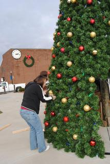 City Clerk Madonna Hornback helps decorate the tree.