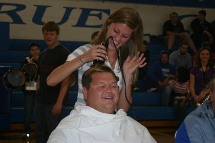 Katey Skees took a turn at the clippers, giving Band Director Jaime Smith a buzzcut.