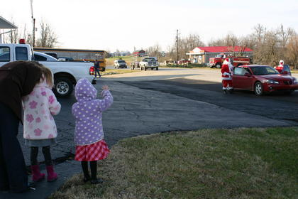 Jaedyn Heckman waved as Santa and Mrs. Claus arrived at Magnolia Firehouse.