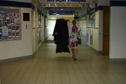 Teacher Katie Cecil carries robes for herself and husband Eric. LCHS teachers wear black robes during commencement.