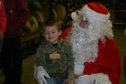 Matthew Meredith, 3, smiles as Santa hands him a bag of Christmas candy.
