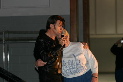 "Elvis dances with an audience member to ""Hound Dog"""