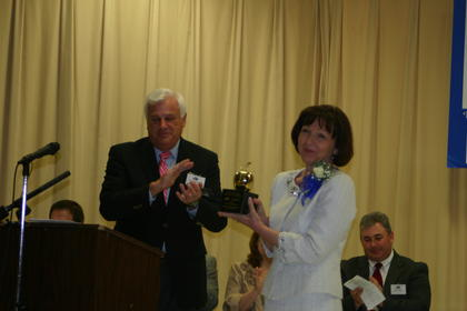 """WHAS-11 anchorman Gary Roedemeier presented Abraham Lincoln Elementary School teacher Lisa Hawkins, right, the """"golden apple"""" award. Hawkins was named the 2013 LaRue County Schools ExCEL Teacher of the Year."""