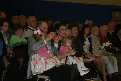 Family members of Lisa Hawkins gathered in the Abraham Lincoln Elementary School gym Wednesday morning for the ExCEL ceremony. From left, her husband, Glenn Hawkins, tries to take a photo while balancing granddaughter Katherine Hawkins on his lap; daughter-in-law, Lisa Hawkins with her daughter, Victoria; mother-in-law, Odell Hawkins; Sue Ann Breeze; daughter, Addie Hawkins, uncle, LeRoy Gardner; uncle, Richard Mathieson; and brother, Gordon Thomas with his wife, Lori Thomas.