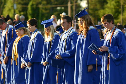 Graduates stood during a moment of silence observed for the late Nathan McCurry.