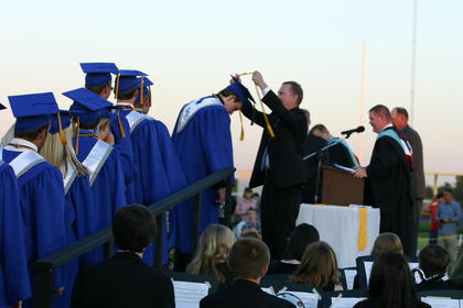 Superintendent Sam Sanders places a gold honor cord on Valedictorian Tyler Skaggs.