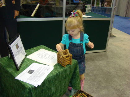 Kristen Shepherd built her first log cabin at the LaRue County booth at the State Fair.