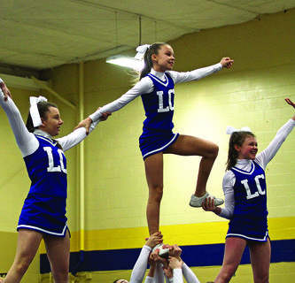 LaRue County Middle School Cheerleaders Kaylee Hornback, Destiny Kirby and Emma Bowling stunt during Saturday's competition.