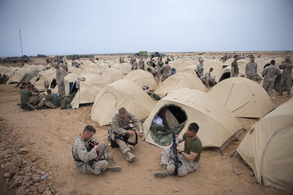 Marines clean their weapons, talk and find other ways to spend their off-duty time while deployed to southern Morocco during African Lion 2011. While in the Cap Draa training area they experienced sandstorms, the rain showers of the wet season and the heat that traditionally goes with a desert.