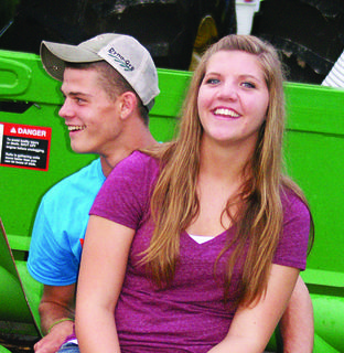 Brooklyn Armstrong and Caleb Kirkpatrick sit together on a combine during AGstravaganza.