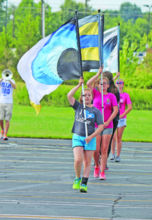 Savannah Smith, followed by Brittany Grant, leads the color guard during band camp.
