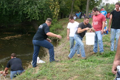 """""""Massey's Gang"""" works on getting their buckets of water filled and poured into a tub at the top of the bank at Creekfront, during the Pioneer Games on Saturday Oct. 5."""