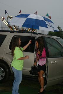 LaRue County Fair Board member MaDonna Hornback held an umbrella for a contestant.