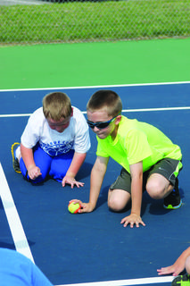Carson DeVary, right,  practices his hand-eye coordination while Baines Turner watches. Turner attended the Tennis Camp for  kindergarten through second-graders.