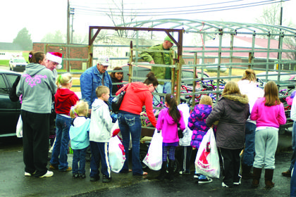 Children gathered around a cattle trailer full of bicycles as volunteers sorted.