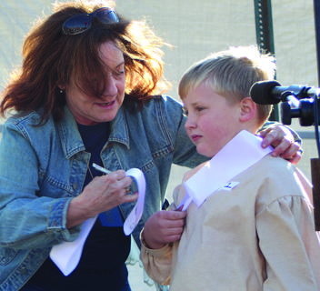 Lincoln Days volunteer Daphne Loyall put a winner's sash on Little Abe, Thomas Ronkainen, 7, of Hodgenville.
