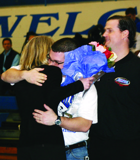 Paul Cooper hugs D.J. Canter during Coach Gary Canter's retirement ceremony. Jim Shaw is at right.