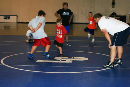 Landon Packard and Connor Lambert played foot tag in Wrestling Skills Camp. Watching the action are coaches Damon Barnes, Elijah Zwiep and Jason Detre.