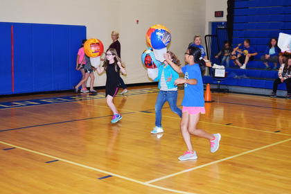 Jessica Serrano, Karlee Thomas and Holly Murray are pictured running in the milk jug relay.