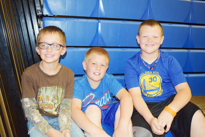 Fourth graders Chase Pellmar, Kyle Henderson and Jake Heady wait on the bleachers as their classmates compete in the milk jug relay.