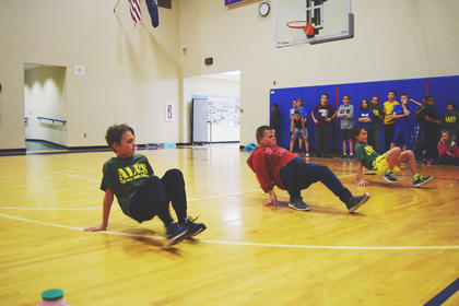 Gabe Fortier, Chase Milby and Madison Lambert scurry across the gym in the crab crawl race.