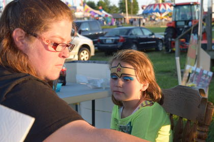 Lizzy Dye is transformed into Wonder Woman at the face painting station in the Kids Zone Friday night at the fair. Kids Zone was sponsored by the LaRue County Public Library.