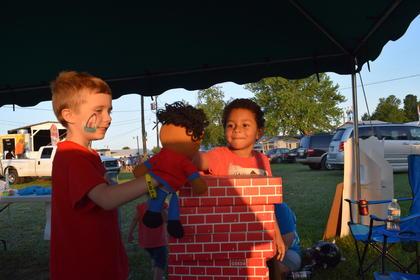Eli Hurst and Conner Pham are pictured playing puppets at the Kids Zone booth.