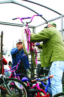 Jimmy Engle II handed a bicycle to his father, Jimmy Engle Sr., outside Magnolia Fire Department. The bikes were delivered to several community stops in a cattle trailer.