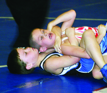 Fourth-grader Thomas Hoppes, bottom, grappled with Blaine Frazier, of Campbellsville, Friday in a youth wrestling match. Hoppes is a student at Hodgenville Elementary School.