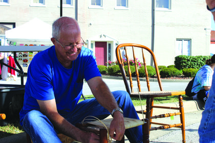 Rob Hutchins of Hodgenville canes a small stool in the heritage demonstration booth on the square Saturday.