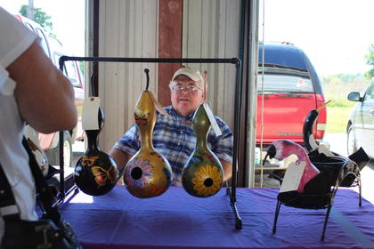 Mickey Bowles is framed between painted gourds at the LaRue County Fall Market.