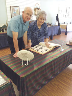 Rob and Nina Hutchins enjoying the 1959 sesquicentennial scrapbook on display in the community room.