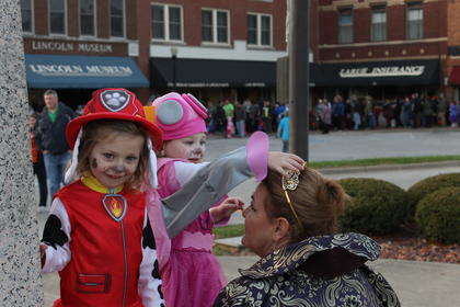 Twin sisters Shelby and Sadie Holbert, 3, adjust the evil queen's crown on the square.