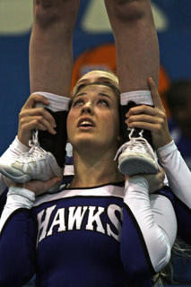 Mallory Skaggs, pictured, and Darienne Grimes are holding Emma Bowling in a single base stunt during the routine.