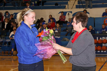 A representative from McDonald's presented Lady Hawk Ivy Brown a certificate and flowers for being nominated for the McDonald's All-American game.