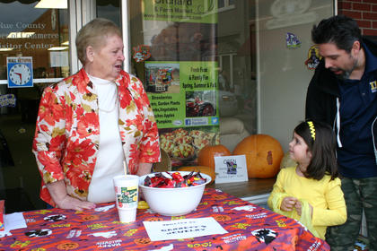 Alyssa Levee trick-or-treated at the LaRue County Chamber of Commerce booth. Dean Henderson is at left.