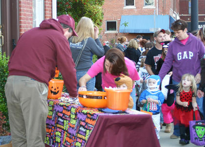 Chuck Crain handed out candy at the Campbellsville University booth. Rhonda Whitlock, Adyson and Case Parker are at right.