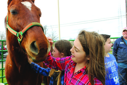 "Kallie Nunn, 10, Rory Cornett, 10, of the 4-H Wranglers horse club and Landon Gomez, 9, interact with ""Duke."